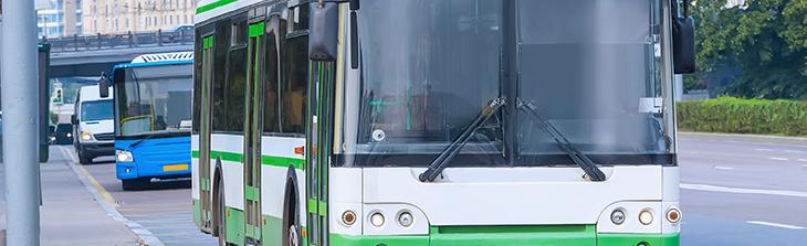 Vehículos de transporte público recorriendo avenida principal